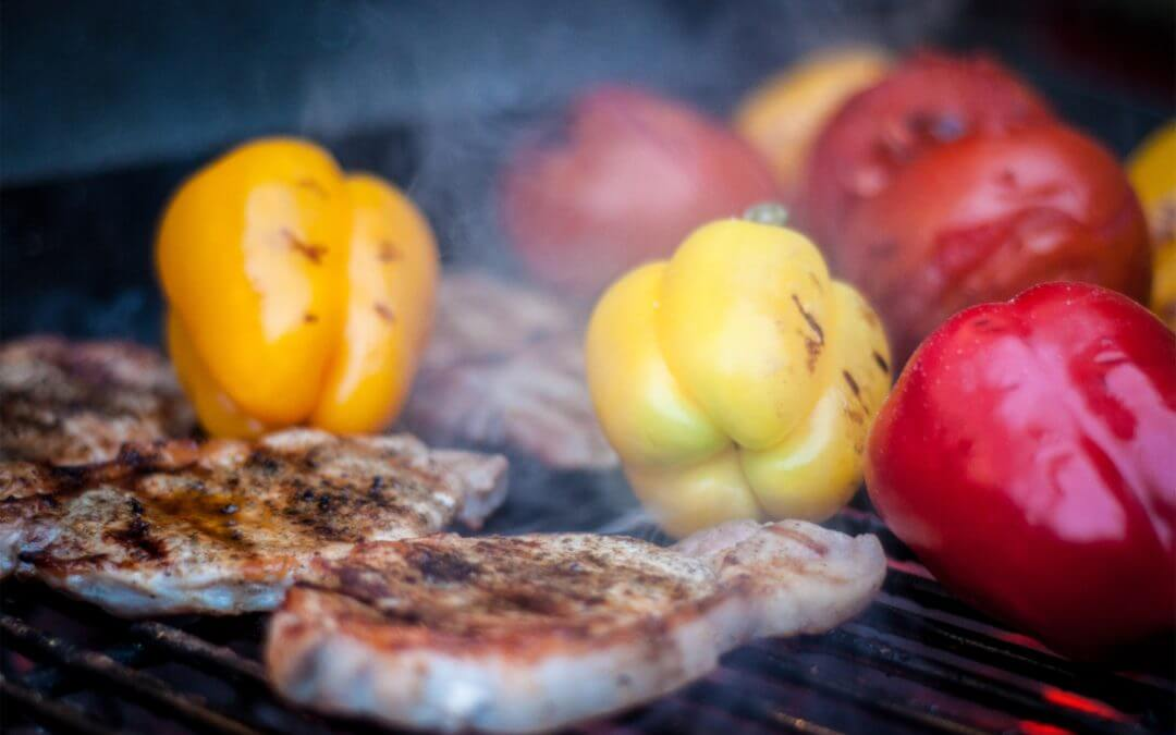 meat and peppers grilling on grill
