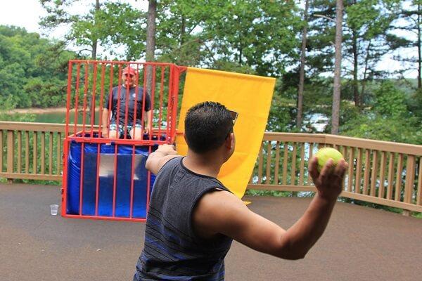 man throwing ball at dunk tank