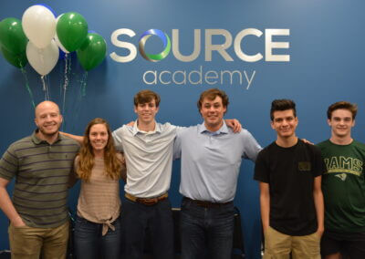 company employees in front of Source Academy wall